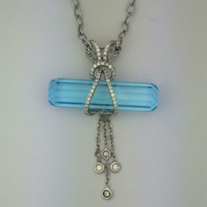 18kt white gold pendant with blue topaz barrel set horizontally. The blue topaz weighs 31.41 carats and is wrapped in diamonds with a diamond tassel. Diamonds are .31 ct total weight.